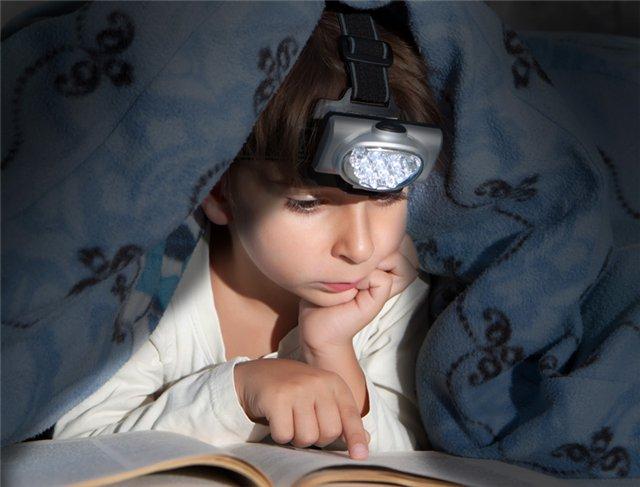 мальчик читает книгу под одеялом