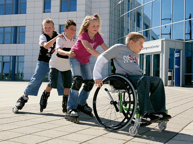 дети катают друга инвалида