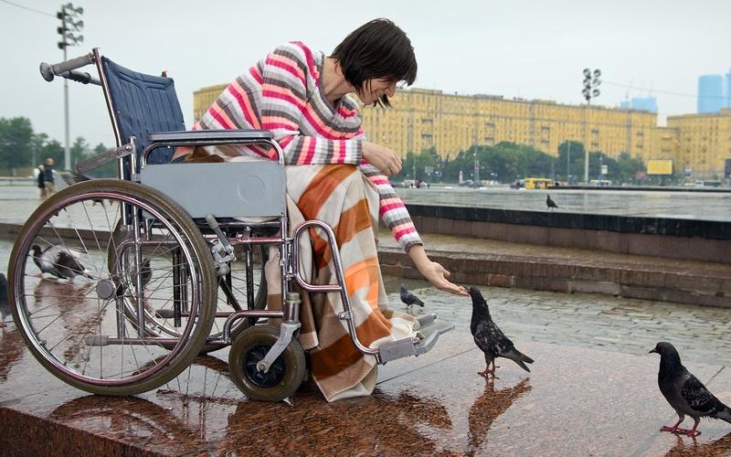 девушка на коляске кормит голубей